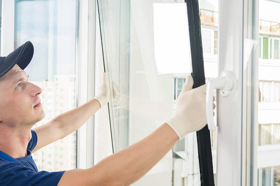 a specialist in installing plastic windows puts a double-glazed